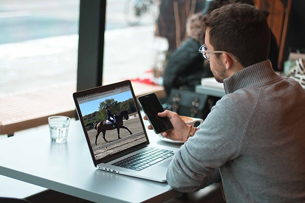 A coach coaching a horse rider during a remote live lesson